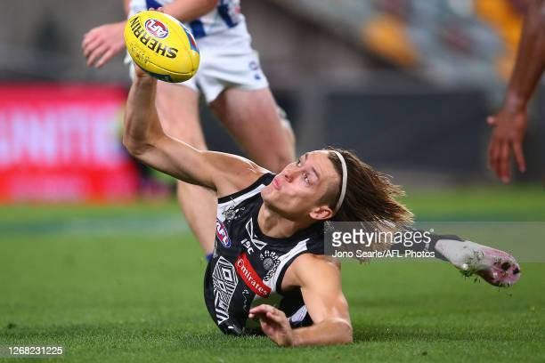 Darcy Moore of the Magpies reaches for the ball during the round 13 AFL match between the Collingwood Magpies and the North Melbourne Kangaroos at...