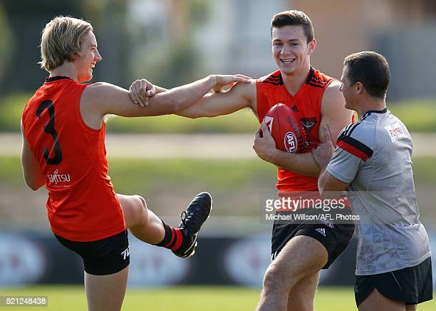 Darcy Parish and Conor McKenna of the Bombers stretch with Paul Turk Senior Strength and Conditioning Coach of the Bombers during an Essendon Bombers...