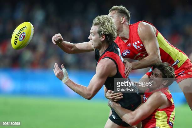 Darcy Parish of the Bombers handballs while tackled during the round 17 AFL match between the Gold Coast Suns and the Essendon Bombers at Metricon...