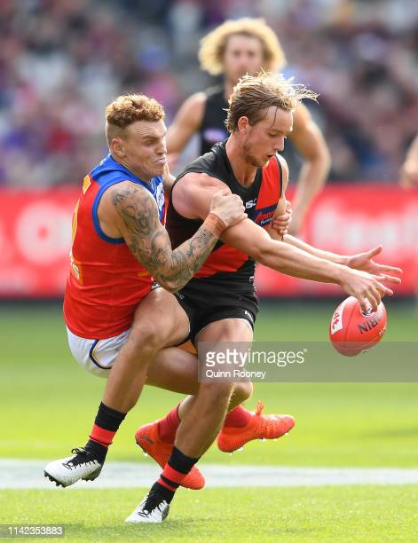 Darcy Parish of the Bombers kicks whilst being tackled by Mitch Robinson of the Lions during the round four AFL match between the Essendon Bombers...