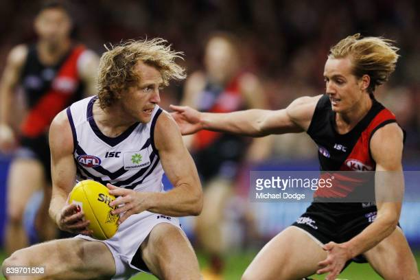 Darcy Parish of the Bombers tackles David Mundy of the Dockers during the round 23 AFL match between the Essendon Bombers and the Fremantle Dockers...