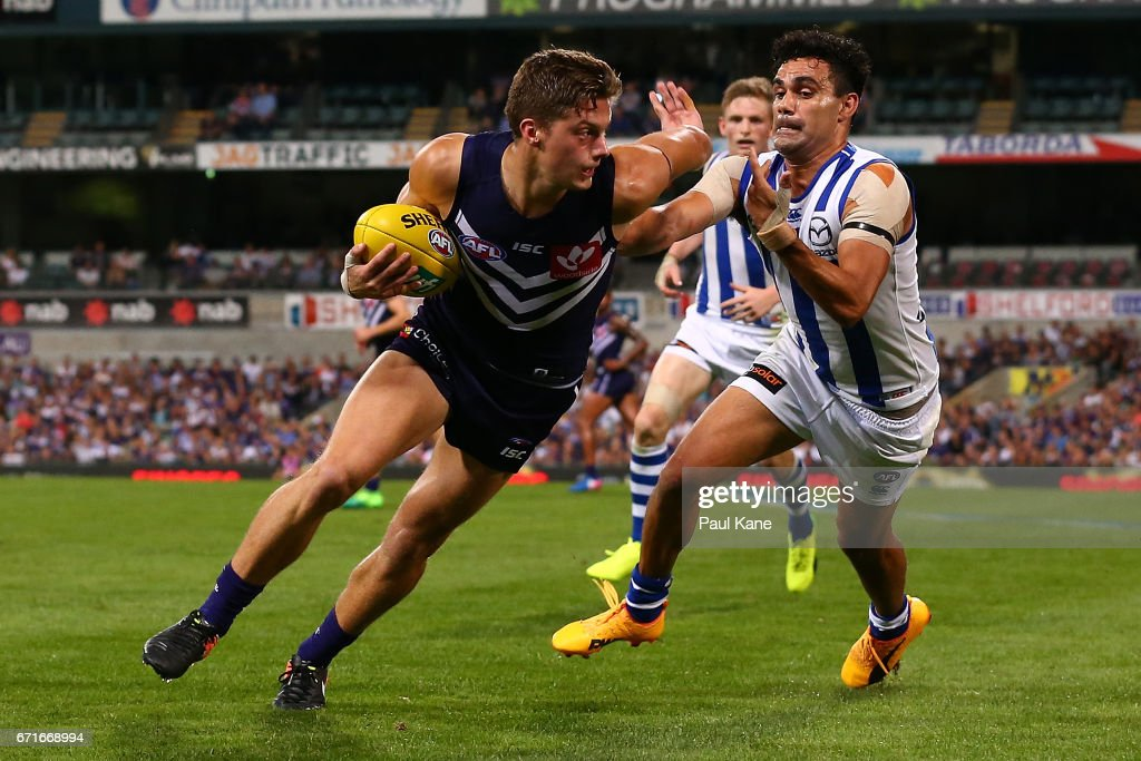Darcy Tucker of the Dockers evades a tackle by Lindsay Thomas of the Kangaroos during the round five AFL match between the Fremantle Dockers and the North Melbourne Kangaroos at Domain Stadium on April 22, 2017 in Perth, Australia.
