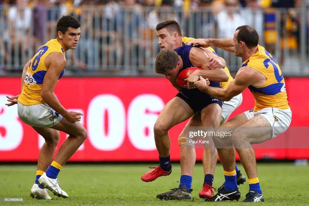Darcy Tucker of the Dockers gets tackled by Elliot Yeo and Shannon Hurn of the Eagles during the Round 6 AFL match between the Fremantle Dockers and West Coast Eagles at Optus Stadium on April 29, 2018 in Perth, Australia.