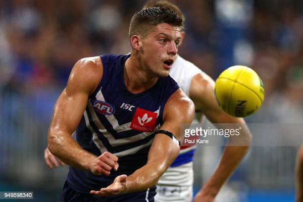 Darcy Tucker of the Dockers handballs during the round five AFL match between the Fremantle Dockers and the Western Bulldogs at Optus Stadium on...