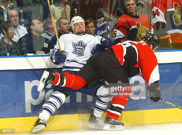 Darcy Tucker of the Toronto Maple Leafs is checked by Wade Redden of the Ottawa Senators during game two of the Eastern Conference Semi Finals at the...