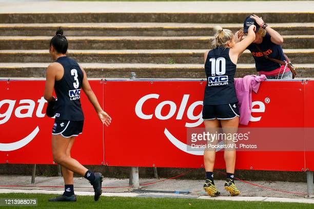 Darcy Vescio of the Blues and Sarah Hosking of the Blues run to friends in the crowd after winning the AFLW Semi Final match between the Carlton...