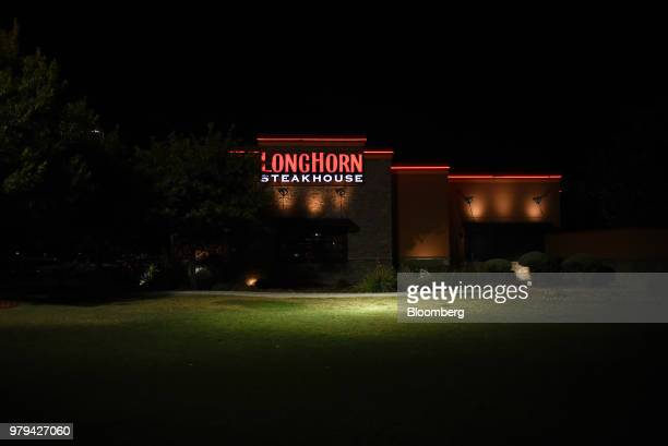 Signage is seen illuminated at night outside a Darden Restaurants Inc Olive Garden location in San Antonio Texas US on Monday June 18 2018 Darden...