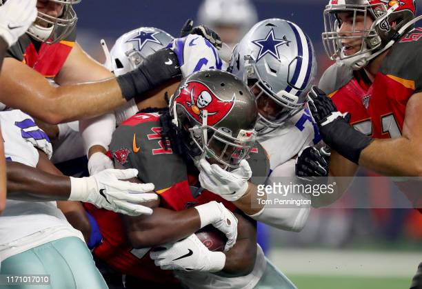 Dare Ogunbowale of the Tampa Bay Buccaneers carries the ball against Cameron Fleming of the Dallas Cowboys and Tyvis Powell of the Dallas Cowboys in...