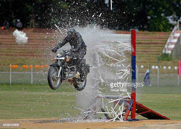 A daredevil of Indian police from Jammu and Kashmir Police wing performs stunt on his motorcycle during India's Independence Day celebrations on...