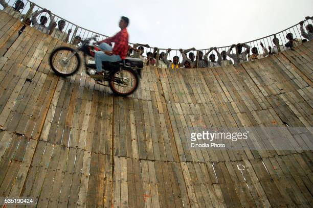 Daredevil performing on motorbike in Well of Death at annual Pandharpur fair in Pandharpur, Maharashtra, India.