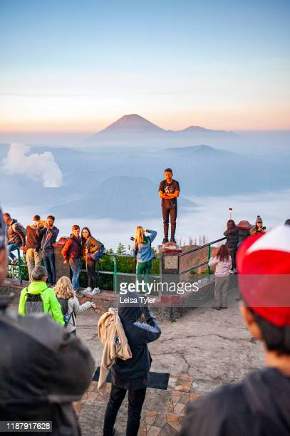 Daredevil tourist stands on a cliff railing during sunrise at Mount Bromo, an active volcano and popular tourist destination in East Java, Indonesia.