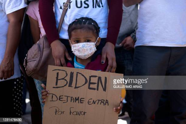Dareli Matamoros, a girl from Honduras, holds a sign asking President Biden to let her in during a migrant demonstration demanding clearer United...