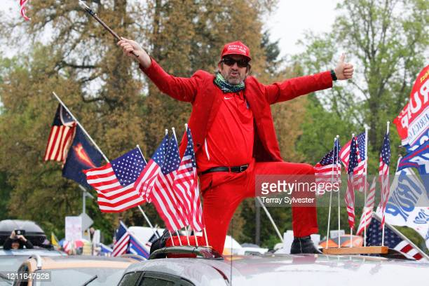 Daren Beck waves an American flag on top of a car at the ReOpen Oregon Rally on May 2, 2020 in Salem, Oregon. Demonstrators gathered at the state...