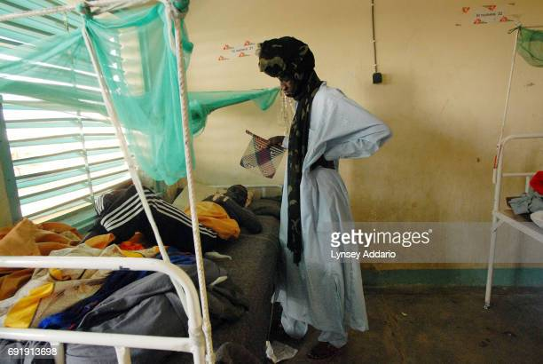 Darfur rebel fans a wounded commrade in a local hospital in Iriba in northeastern Chad October 14 2006 Fierce fighting continues between Sudanese...