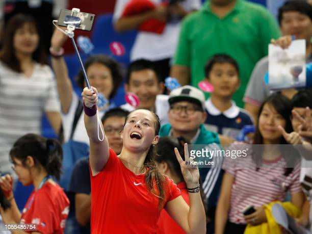 Daria Kasatkina of Russia takes a selfie with spectators after winning the match against Qiang Wang of China during their match on day 1 of 2018 WTA...