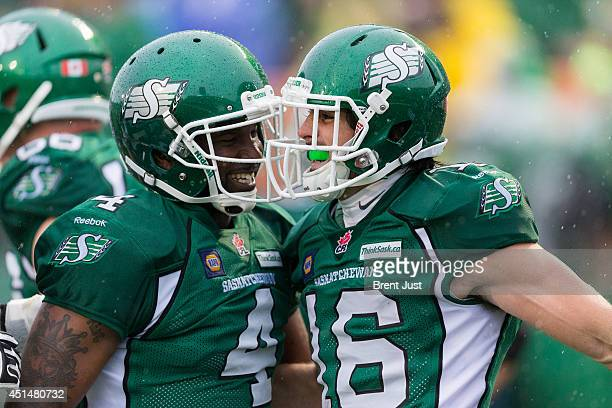 Darian Durant and Brett Swain of the Saskatchewan Roughriders celebrate a touchdown during week one of the 2014 CFL season at Mosaic Stadium on June...