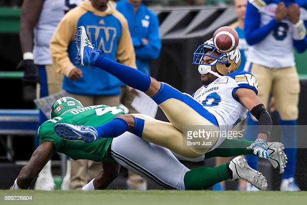 Darian Durant of the Saskatchewan Roughriders hits Johnny Adams of the Winnipeg Blue Bombers and knocks the ball loose after Adams had intercepted a...