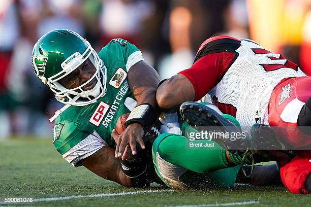 Darian Durant of the Saskatchewan Roughriders is brought down by Charleston Hughes of the Calgary Stampeders after scrambling with the ball in the...