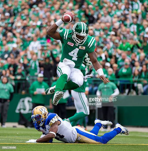 Darian Durant of the Saskatchewan Roughriders leaps over Maurice Leggett of the Winnipeg Blue Bombers for a touchdown in the second half of the game...