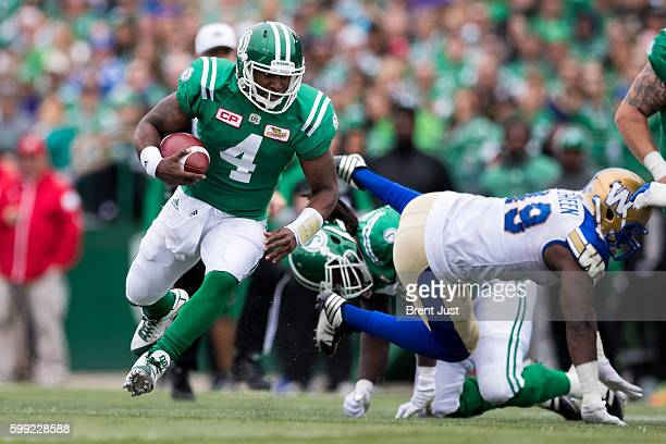 Darian Durant of the Saskatchewan Roughriders scrambles with the ball in the game between the Winnipeg Blue Bombers and Saskatchewan Roughriders at...