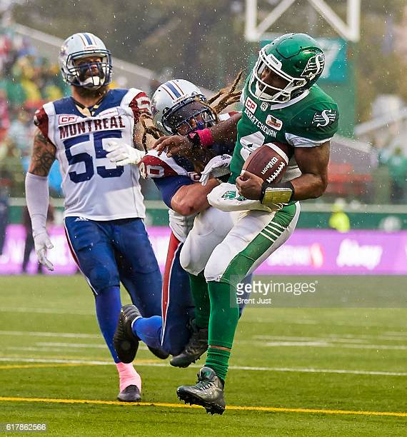 Darian Durant of the Saskatchewan Roughriders takes a hit from Bear Woods of the Montreal Alouettes as he scores a touchdown in the game between the...