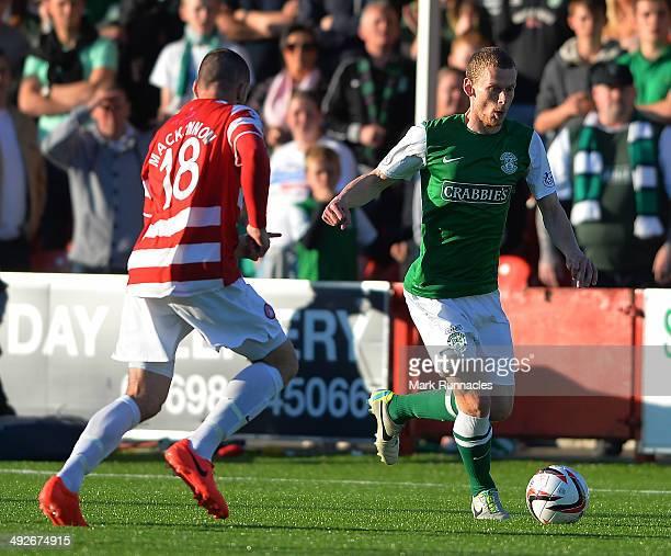 Darian Mackinnon of Hamilton Academical challenges Scott Robertson of Hibernian during the Scottish Premiership Playoff Final First Leg between...