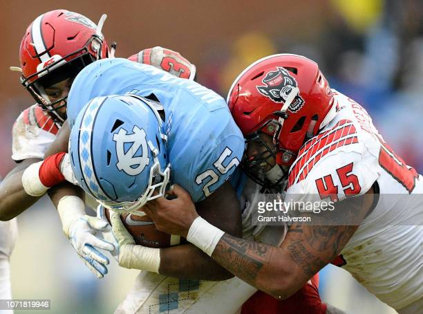 Darian Roseboro of the North Carolina State Wolfpack is called for a facemask penalty as he tackles Javonte Williams of the North Carolina Tar Heels...