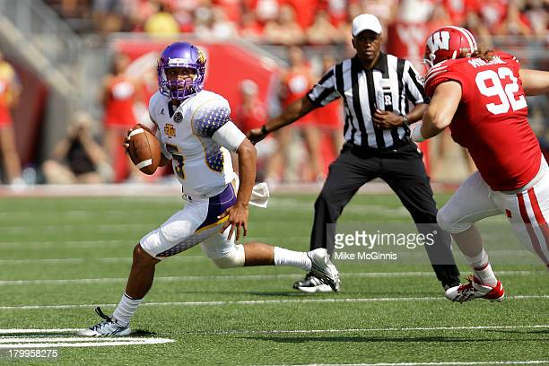Darian Stone of the Tennessee Tech Golden Eagles scrambles out of the pocket with Pat Muldoon of the Wisconsin Badgers in pursuit during the game at...