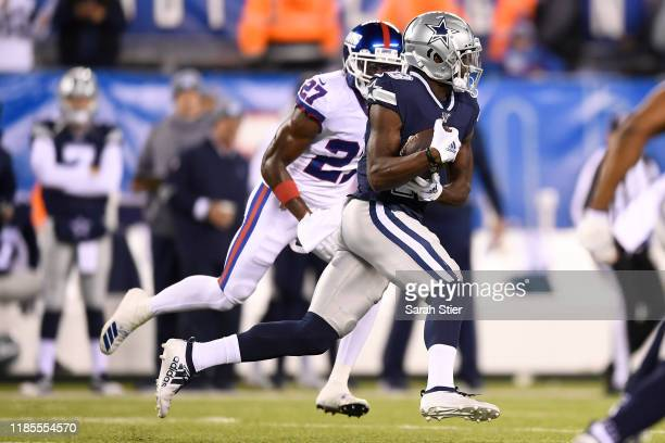 Darian Thompson of the Dallas Cowboys carries the ball as Deandre Baker of the New York Giants defends during the first quarter of the game at...