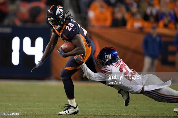 Darian Thompson of the New York Giants stretches to wrap up Jamaal Charles of the Denver Broncos during the third quarter of the on Sunday October 15...