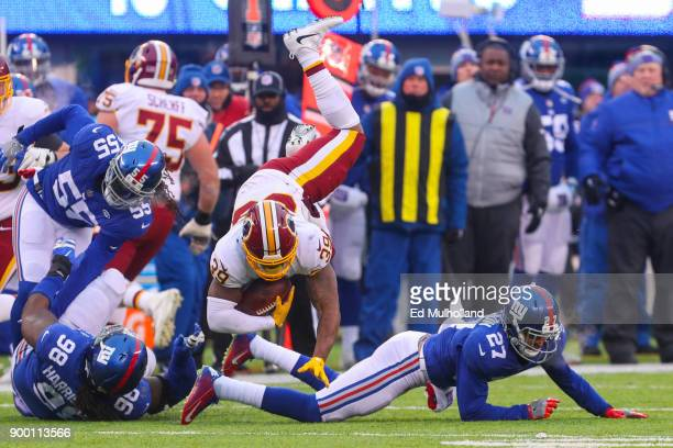 Darian Thompson of the New York Giants tackles Keith Marshall of the Washington Redskins during the second half at MetLife Stadium on December 31...