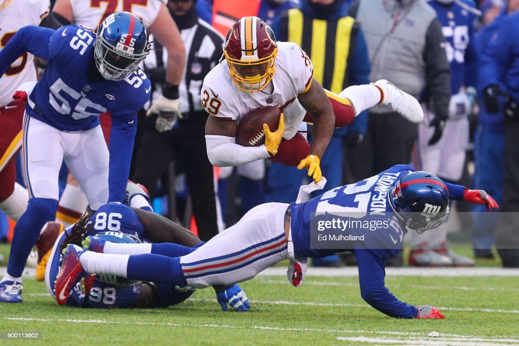 Darian Thompson #27 of the New York Giants tackles Keith Marshall #39 of the Washington Redskins during the second half at MetLife Stadium on December 31, 2017 in East Rutherford, New Jersey. The Giants defeated the Redskins 18-10.