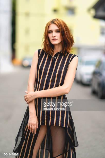 Dariana Cerciu wears a striped sleeveless dress with black lace black heels shoes during Feeric Fashion Week 2018 on July 22 2018 in Sibiu Romania