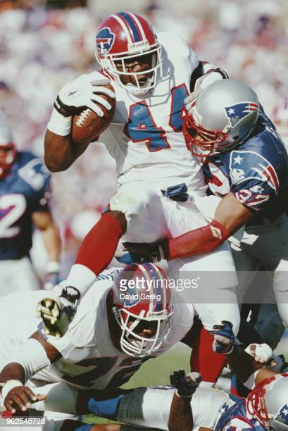 Darick Holmes Running Back for the Buffalo Bills is tackled by Willie Clay Defensive Back for the New England Patriots during the American Football...