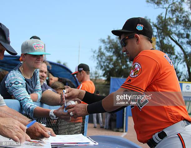 Dariel Alvarez of the Baltimore Orioles signs autographs before the game against the Toronto Blue Jays at Florida Auto Exchange Stadium on March 4...
