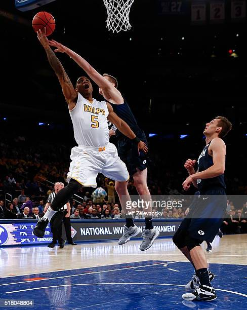 Darien Walker of the Valparaiso Crusaders drives against Kyle Davis of the Brigham Young Cougars during their NIT Championship Semifinal game at...