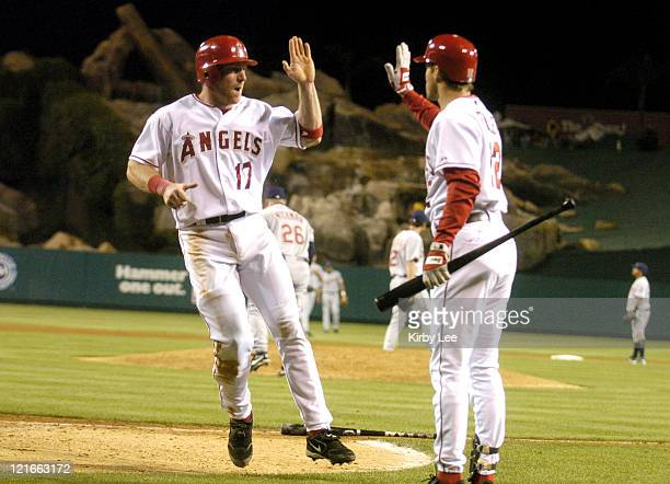 Darin Erstad of the Los Angeles Angels of Anaheim exchanges high five with Steve Finley after scoring from second base in the ninth inning with two...