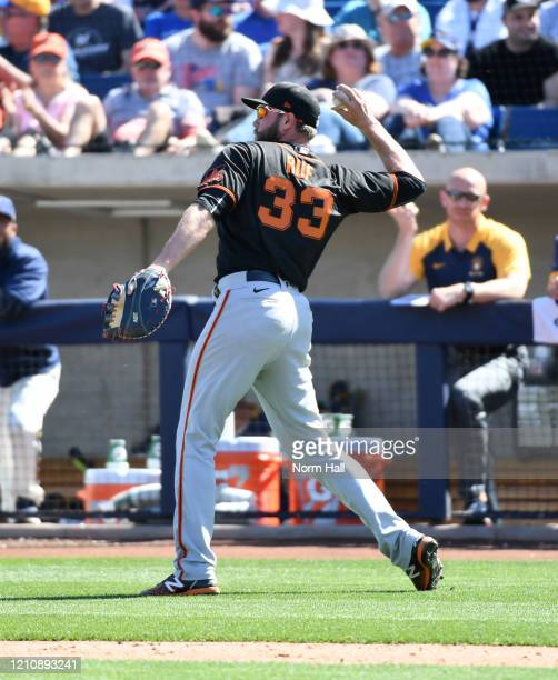 Darin Ruf of the San Francisco Giants throws the ball to first base against the Milwaukee Brewers during a spring training game at American Family...
