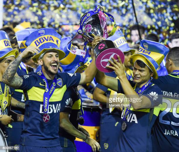 Dario Benedetto and Gustavo Bou of Boca Juniors lift the trophy to celebrate after a match between Boca Juniors and Union as part of Torneo Primera...