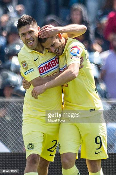 Dario Benedetto of America celebrates with his teammate Oribe Peralta after scoring the first goal of his team during a match between Pumas UNAM v...