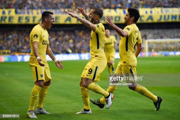 Dario Benedetto of Boca Juniors celebrates with teammates Cristian Pavon and Pablo Perez after scoring the first goal of his team during a match...