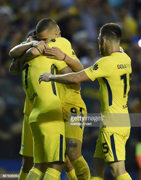Dario Benedetto of Boca Juniors celebrates with teammates Cristian Pavon Leonardo Jara and Nahitan Nandez after scoring the third goal of his team...