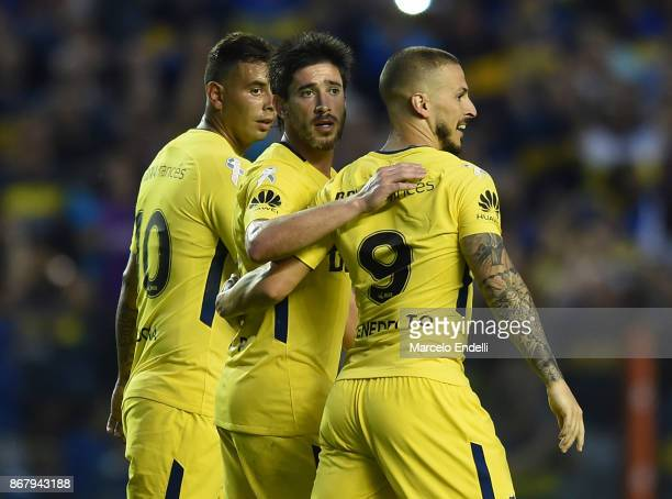 Dario Benedetto of Boca Juniors celebrates with teammates Edwin Cardona and Pablo Perez after scoring the third goal of his team during a match...