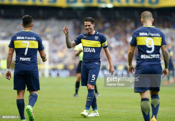 Dario Benedetto of Boca Juniors celebrates with teammates Fernando Gago and Cristian Pavon after scoring the first goal of his team during a match...