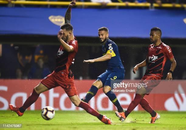 Dario Benedetto of Boca Juniors kicks the ball against Léo Pereira and Renan Lodi of Atletico Paranaense during a group G match between Boca Juniors...