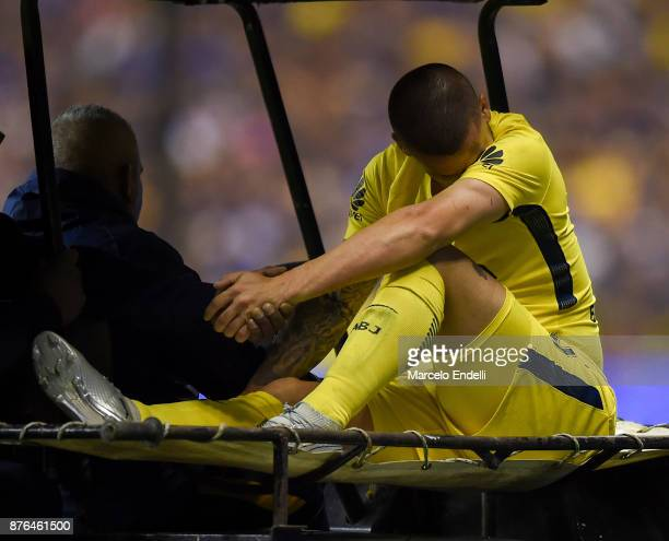 Dario Benedetto of Boca Juniors leaves the field after being injured during a match between Boca Juniors and Racing Club as part of the Superliga...