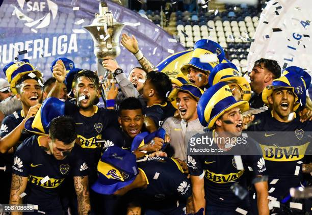 Dario Benedetto of Boca Juniors lifts the trophy to celebrate with teammates after winning the Superliga 2017/18 against Gimnasia y Esgrima La Plata...