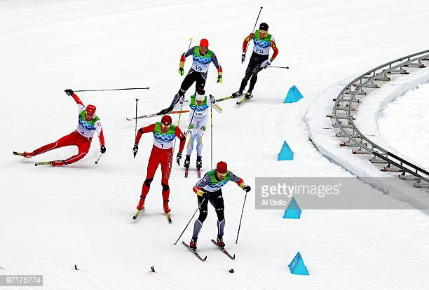 Dario Cologna of Switzerland crashes to the snow as Petter Northug of Norway competes on his way to winning the gold medal from Axel Teichmann of...