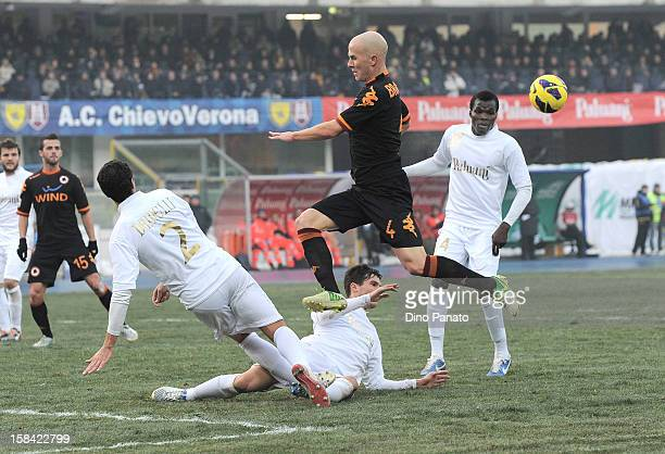 Dario Dainelli of Chievo Verona competes with Michael Bradley of AS Roma during the Serie A match between AC Chievo Verona and AS Roma at Stadio...