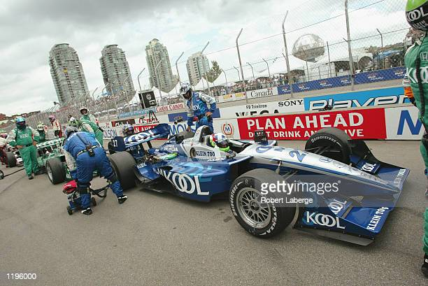 Dario Franchitti and his Team KOOL Gren teammate Paul Tracy wait in the pits after the race is red flagged for an accident with seven laps remaining...